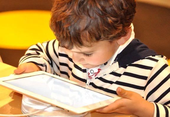 niño viendo series en una tablet con los códigos de netflix
